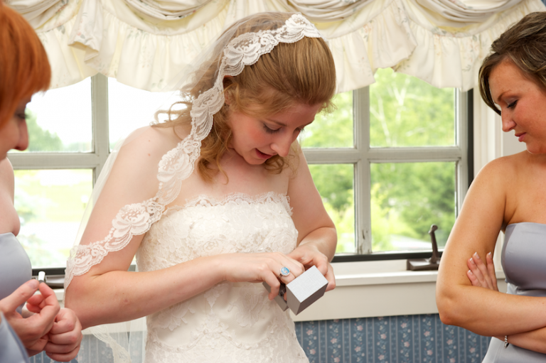 bride puts on earrings before wedding