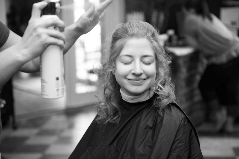 bride getting hair done before wedding