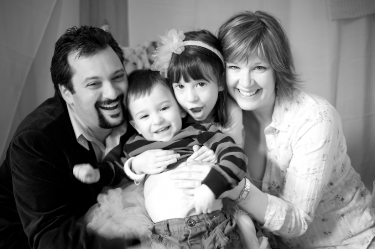 black and white portrait of smiling family tickling brother's belly