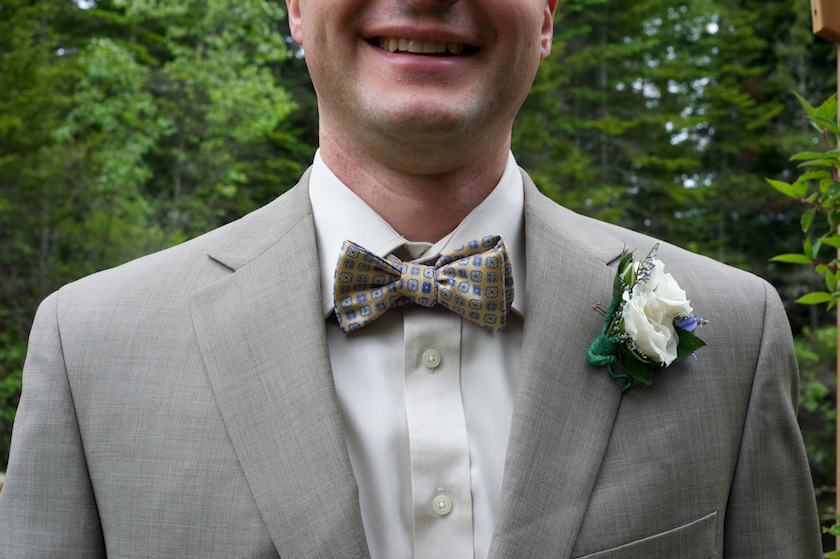 groom wears a bow tie with gray suit