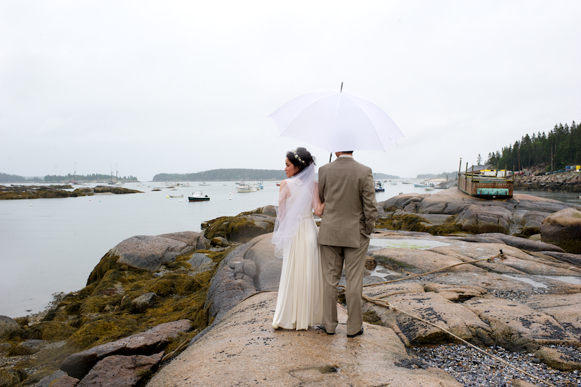 bride looks to the side while sharing umbrella