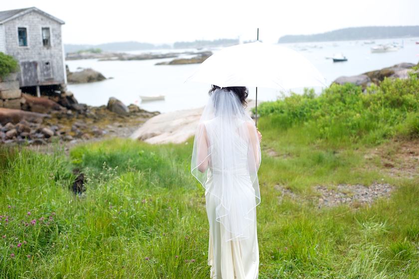 bride walks to ocean with umbrella