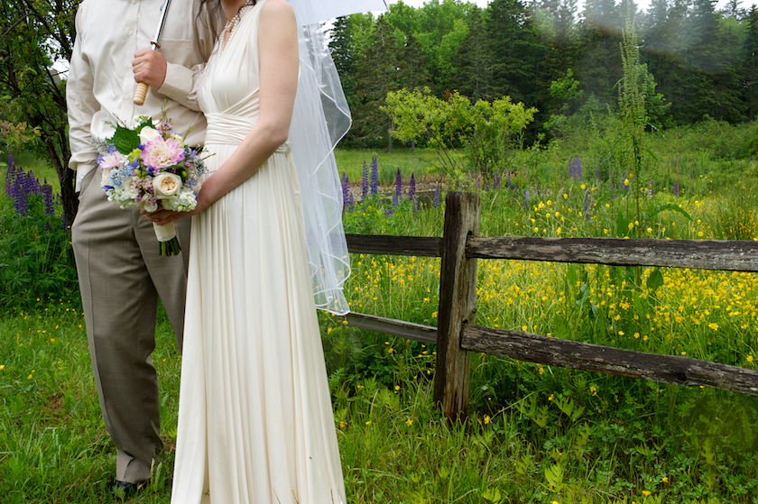 bride and groom at a roadside fence