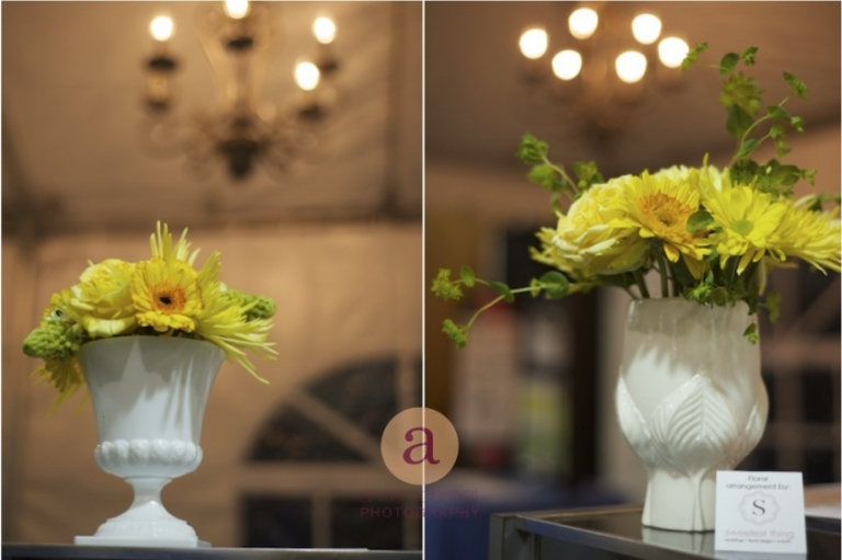 yellow flowers in milk glass under chandelier