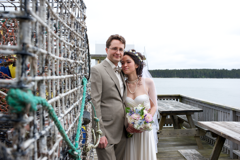 bride and groom on dock with lobster traps
