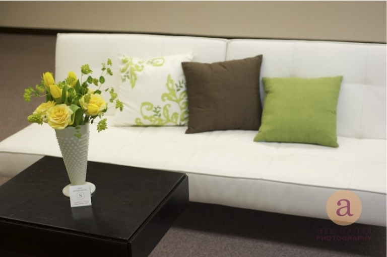 white couch with green pillows and yellow flowers
