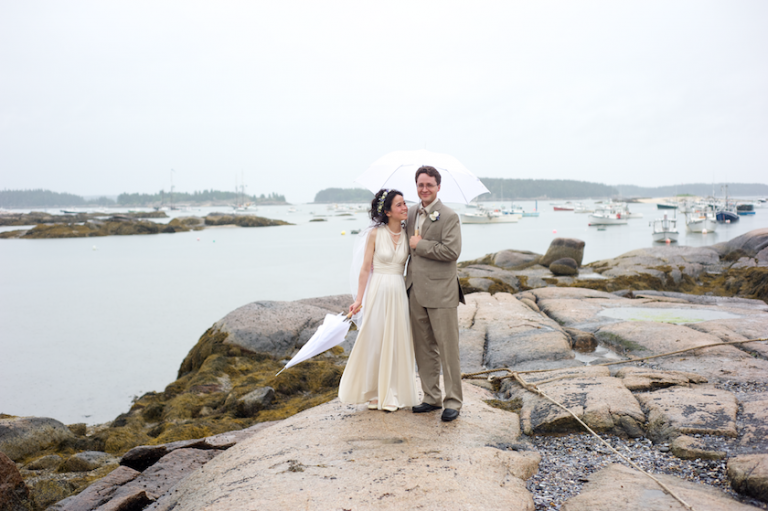 bride and groom share umbrella at the ocean
