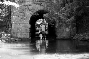 Maine engagement photo under stone train trestle