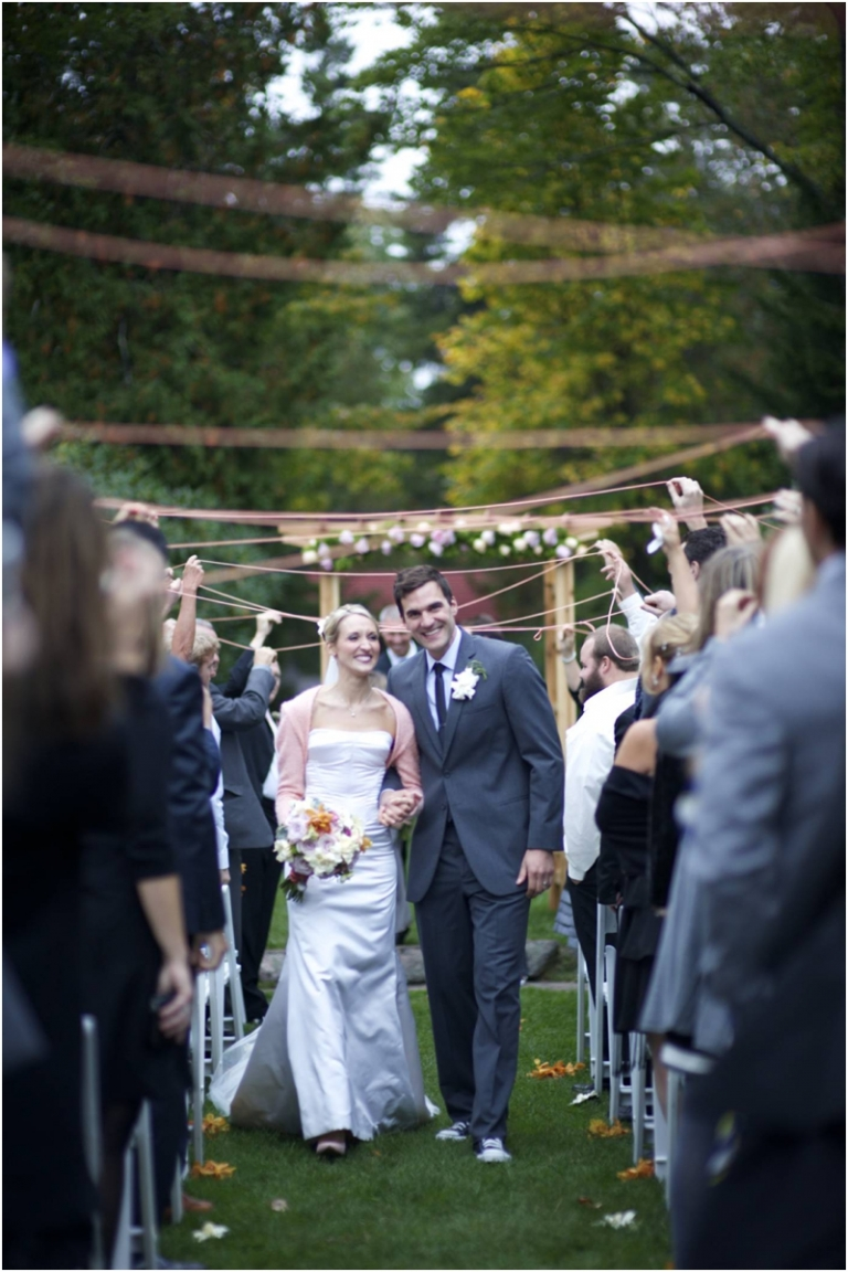 bride and groom walk under a ribbon canopy at ceremony