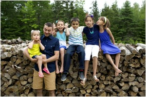 kids with dad in front of the wood pile