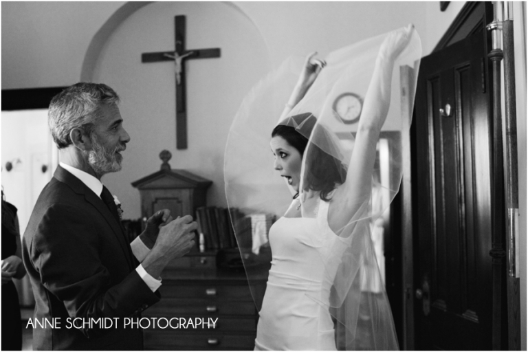 bride lifts veil for father before wedding